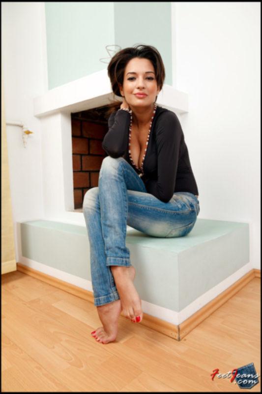 Красивая девушка в джинсах показывает ноги
